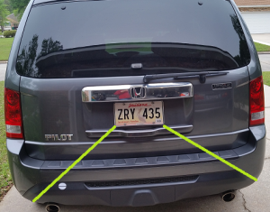 Place decal, horizontally, somewhere along the green line between the corner of the license plate and the corner of the bumper. Either side is acceptable.
